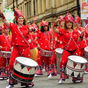 Drummers by Yvonne Katcher - City,  Street & Park  Street Scenes ( signs, building, red, road, drums, women )