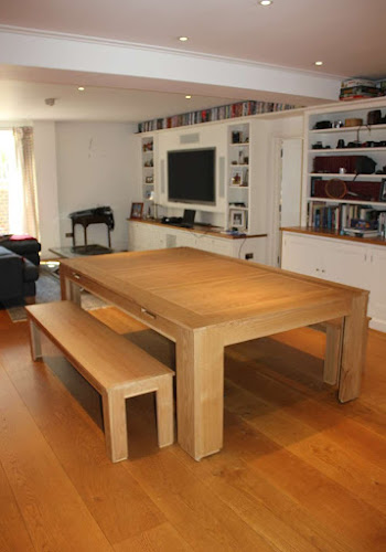 the light wooden spartan dining table on a wooden floor in a lounge area