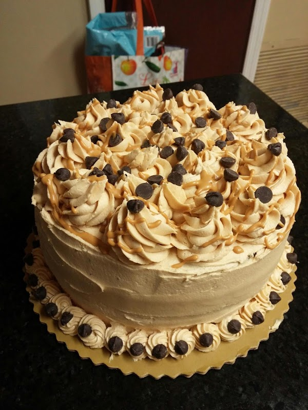 Microwave remaining dulce de leche and drizzle over cake. Decorate with additional chopped dark...