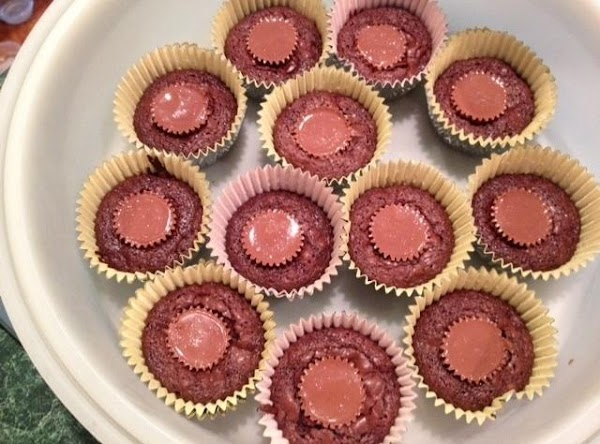 Remove brownie cups from oven.  Immediately place one peanut butter cup in center...