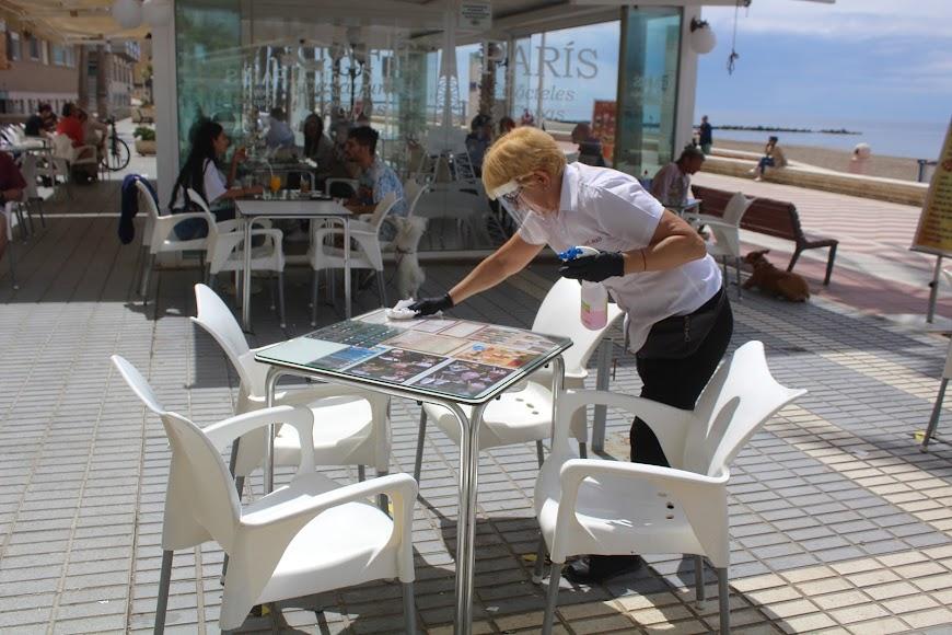 Desinfectando mesa y sillas en Café París.