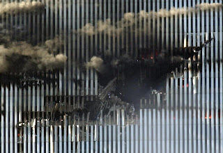 Photo: This file photo shows the impact site of American Airlines Flight 11 in the north tower of the World Trade Center in New York. A person stands at the bottom center of the tear in the building.