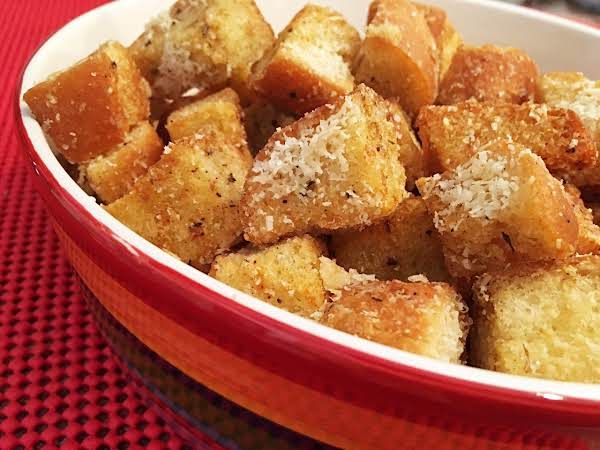 Croutons With Cheese In A Red Serving Bowl On A Red Table Mat.