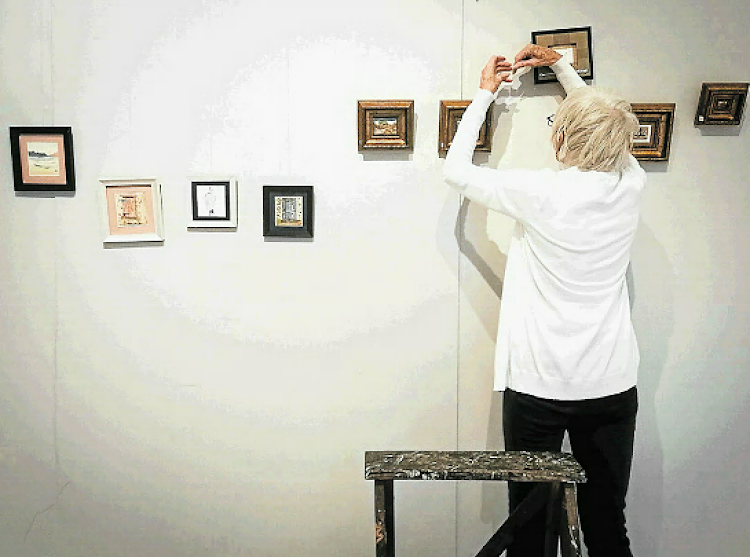 East London Fine Art Society member Anne Baker is hard at work hanging up various small-scale and miniature artworks, transforming the Ann Bryant Art Gallery's Coach House into a room full of little worlds ahead of the Peep Show Exhibition opening at 6.30 pm on Thursday.