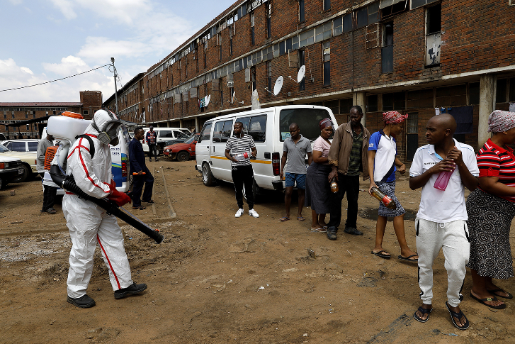 Members of the health services disinfect the Madala hostel in Alexandra, Johannesburg, as the government tries to control the outbreak of Covid-19.