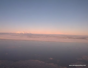 Photo: Approaching Anchorage, we could see across the Cook Inlet to a distant Denali (Mt. McKinley), the right-most peak in the background