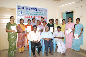 Photo: Participants(standing) holding aloft their certificates earned on completion of their training at GOODWILL