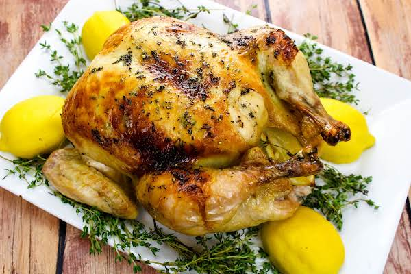Maple-butter Roasted Chicken On A Serving Tray With Thyme And Lemons.