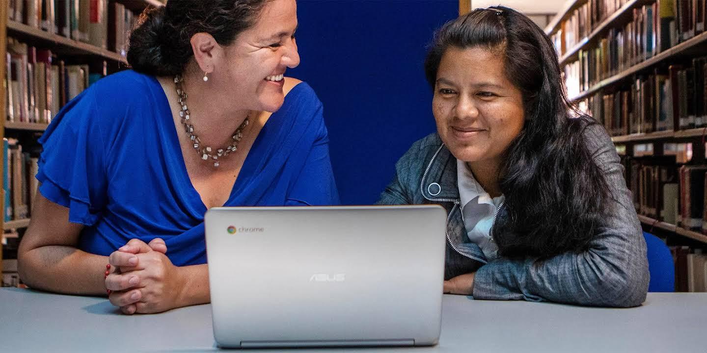 Dos mujeres se encuentran en una biblioteca mirando alegremente la pantalla de un Chromebook.