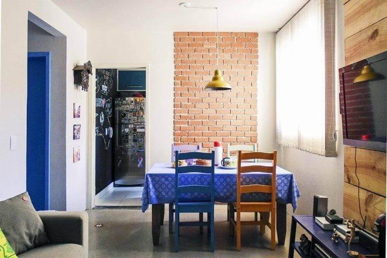 Os moradores optaram um tipo de revestimento para dar um toque descontraído na parede da sala de jantar.