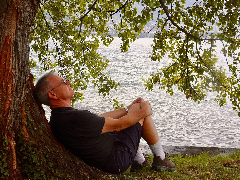 elderly gentleman laying comfortably against a tree in front of cool water demonstrating the effects of cbd