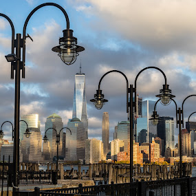 NYC in the distance by Rusty Goris - City,  Street & Park  Skylines ( new york skyline, sunset, liberty state park, nyc, new york city, freedom tower, street lights )
