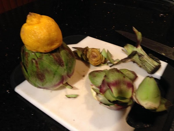 NOW ITS TIME TO PREP ARTICHOKES...WITH A SERRATED KNIFE TRIM OFF TOPS OF ARTICHOKES...