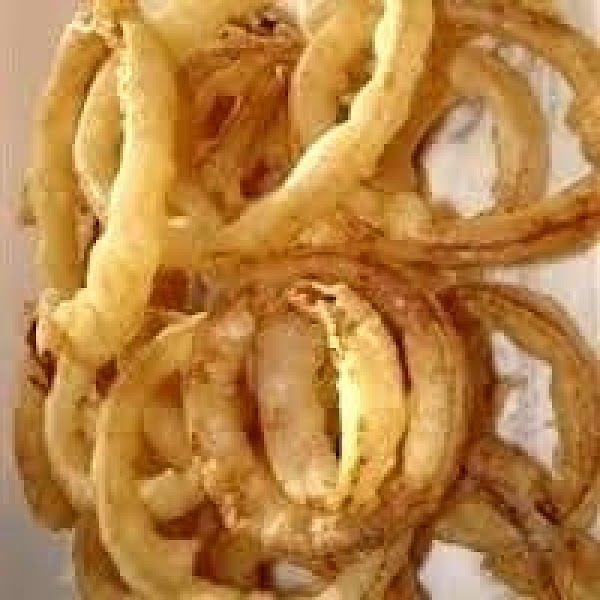 Drop dredged onion slices  - 3 or 4 at a time - into...