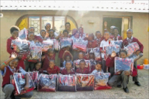 THANK YOU: Excited children - most of them orphaned by the Aids epidemic - at the Hope Children's  Centre in Soshanguve, Pretoria, after Mama Angel donated blankets to them. 12/05/2009. Pic. Peggy Nkomo. © Sowetan.