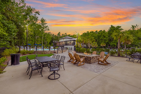 Poolside putt-putt golf, firepit area with adirondack chairs, and outdoor table with chairs at dusk