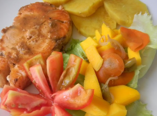 Vanillated Spicey Salmon served with boiled sweet potatoes, vegetable pickled mangoes on a bed of lettuce and salad tomatoes