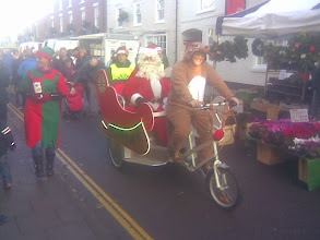 Photo: Santa being rickshawed round by a pedalling reindeer., probably under threat of becoming a venison burger..