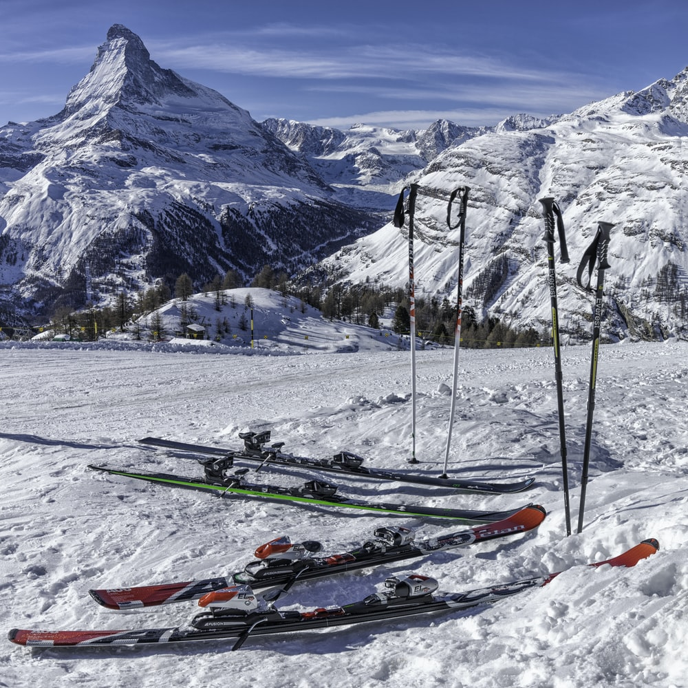 two pairs of red and green skis near mountain covered by snow at daytime