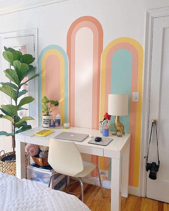 Parede pintada com formas coloridas trouxe alegria ao quarto.
