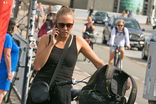 Smartphone? Check. Bicycle? Check. A Danish woman in downtown Copenhagen.
