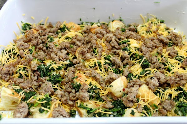 Sausage and cheese sprinkled into baking dish.