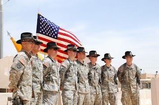 Image of a US Army helicopter cavalry unit posing next to American flag.