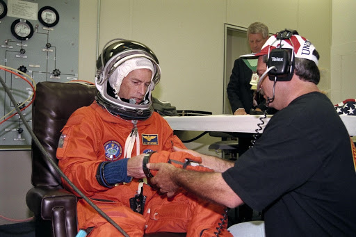 Commander James D. Wetherbee gets help while donning the gloves of his launch and entry suit in the Operations and Checkout Building.