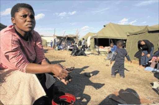 DESTITUTE: Nina Nyamushu sits outside one of the tents provided by NGOs after the eviction of squatters in Marlboro, northern Johannesburg, three weeks ago. PHOTO: Tsheko Kabasia