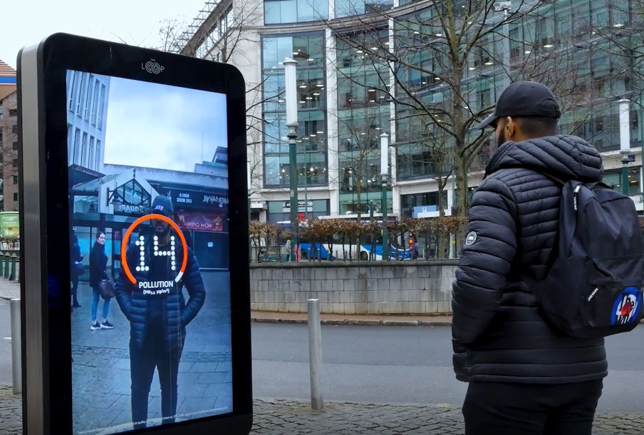 Man looking at a digital billboard that is telling him how much pollution he's breathing in at that moment. The billboard displays 14