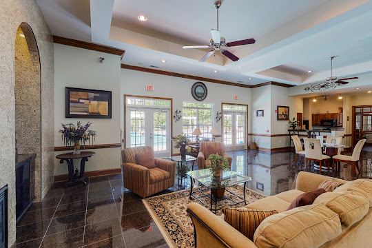 Community clubhouse with comfy lounge seating, tall ceilings, and windows viewing the pool