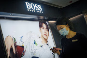 A woman walks past a store of German fashion house Hugo Boss in Beijing, China on March 27, 2021.