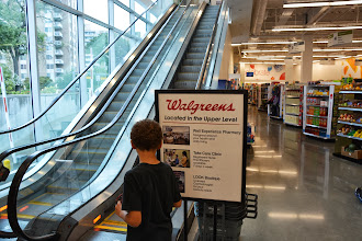 Photo: When I walked in, the first thing I saw were the escalators and a sign directing people upstairs to the Healthcare Clinic.