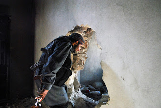 Photo: A Free Syrian Army rebel fighter passes through a hole punched into the wall of a building in Aleppo, Syria. These 'mouseholes' allow Syrian rebel fighters to navigate the frontlines of battle undetected by government forces. Aleppo, SYRIA - 11/4/2013. Credit: Ali Mustafa/SIPA Press