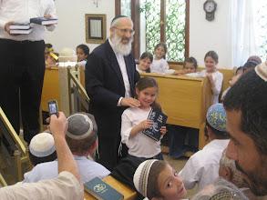 Photo: Reut receives her siddur from Rav Aviner