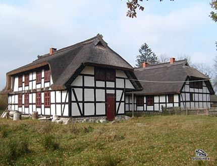 Dwa duże piętrowe domy z muru pruskiego z czerwonymi oknami kryte dachem trzcinowym