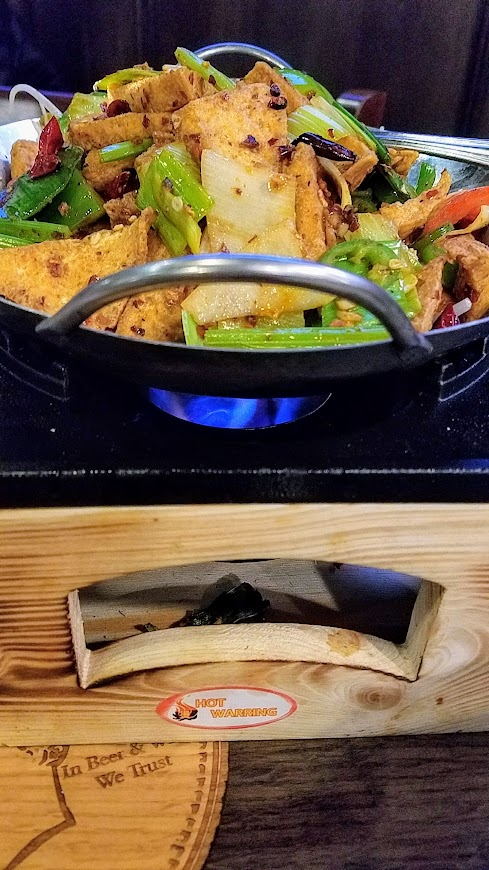 Szechuan Hot and Spicy Dried Pot with here Tofu or other choice of protein, served with bean sprout, celery, bamboo shoots, leeks and bell pepper sizzling at Duck House Portland