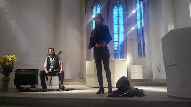 Photo: Doreen Wolff bei ihrer Rede zur Ausstellungseröffnung, im Hintergrund Benni Cellini mit seinem E-Cello