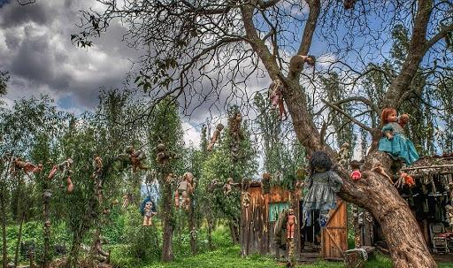 Munecas colgadas en los arboles frente a una casa