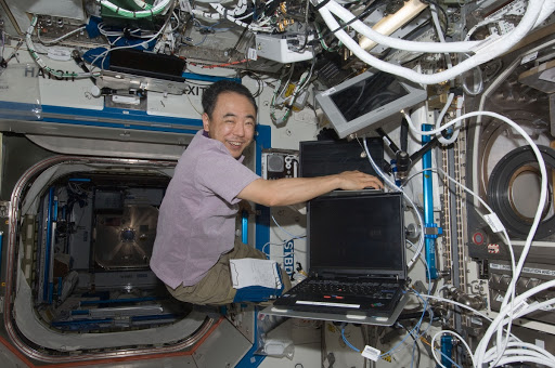 Satoshi Furukawa uses a computer to activate the Microgravity Science Glovebox MSG located in the Destiny laboratory of the International Space Station.
