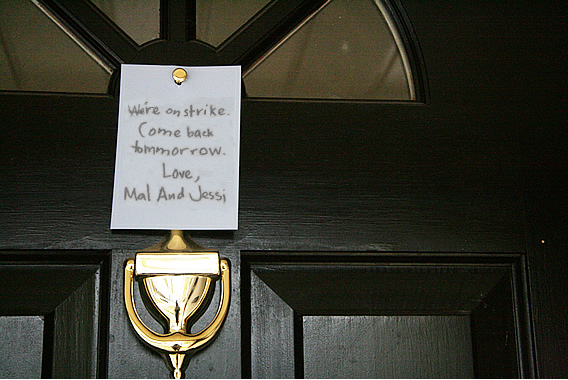 An image of a closed front door. A note in Mal's handwriting is stuck to it saying 'We're on strike. Come back tomorrow. Love Mal and Jessi.'