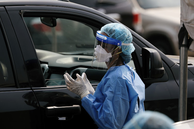 A health worker holds a sample beside a car at a coronavirus drive-through sample collection centre in Abuja, Nigeria on January 14 2021.