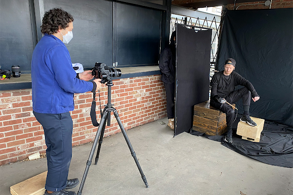 A behind the scenes photo of Justin Kaneps taking a portrait of Jason Barnes. Jason poses against a black backdrop.