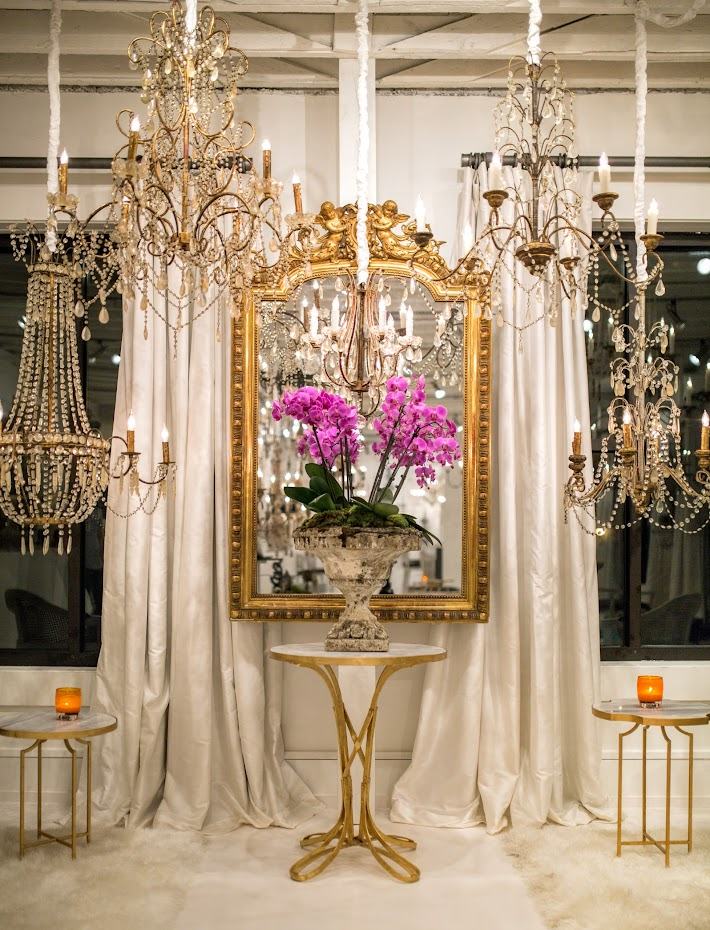 Gorgeous beaded chandeliers by Aidan Gray displayed with gold tables and fanciful French mirror. #aidangray #chandeiler #goldtable