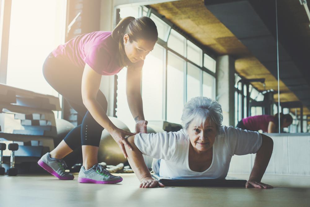 professora ajudando senhora idosa a fazer exercício