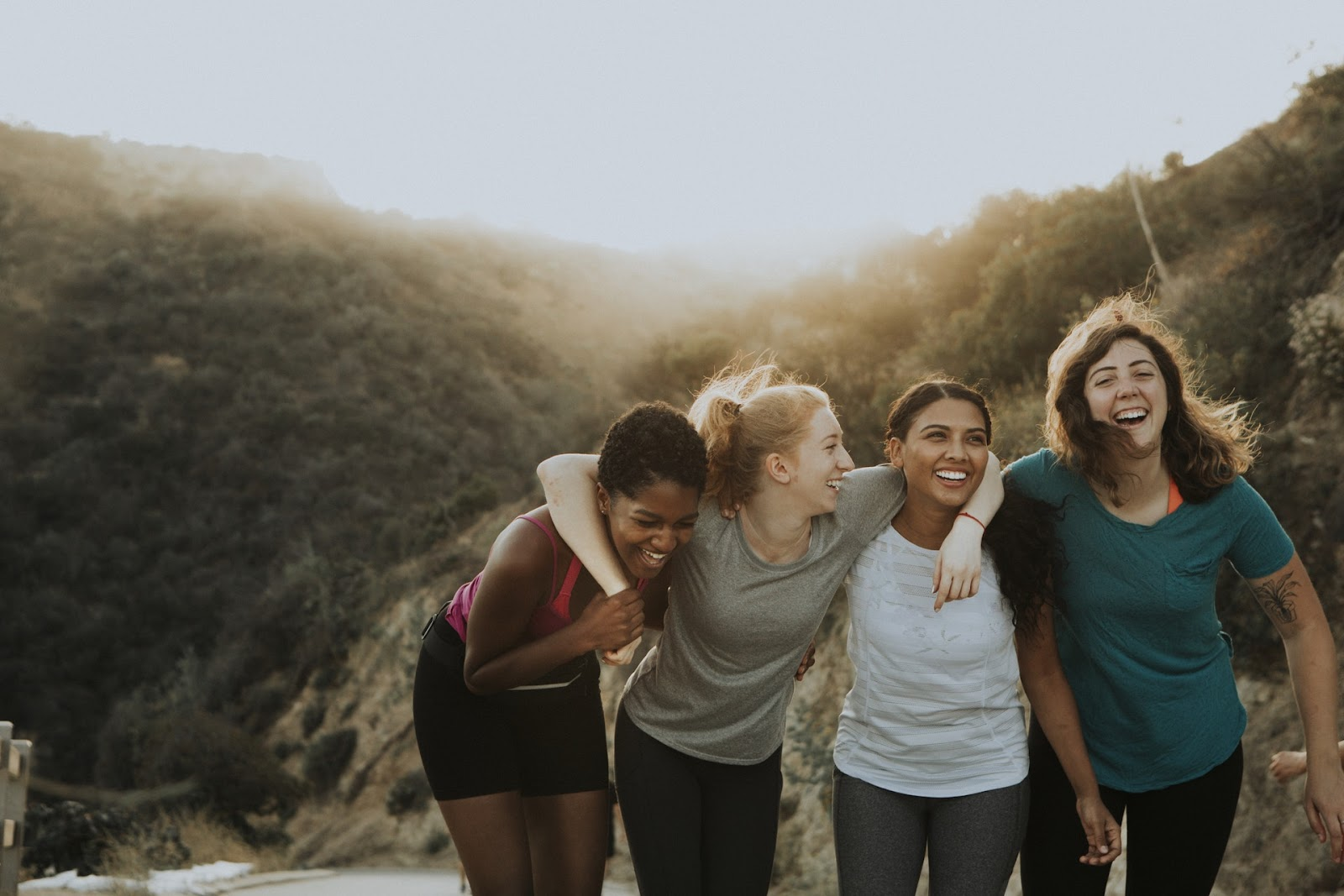 four women on a trail, smiling with their arms around each other