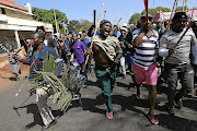 Protesters from various hostels  march along Jules Street in Johannesburg. Carrying weapons,  the men sang, 'foreigners must go back to where they came from'.  Alon Skuy