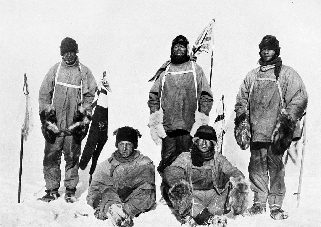 Five men in heavy polar clothing. All look unhappy. The standing men are carrying flagstaffs and a Union flag flies from a mast in the background.