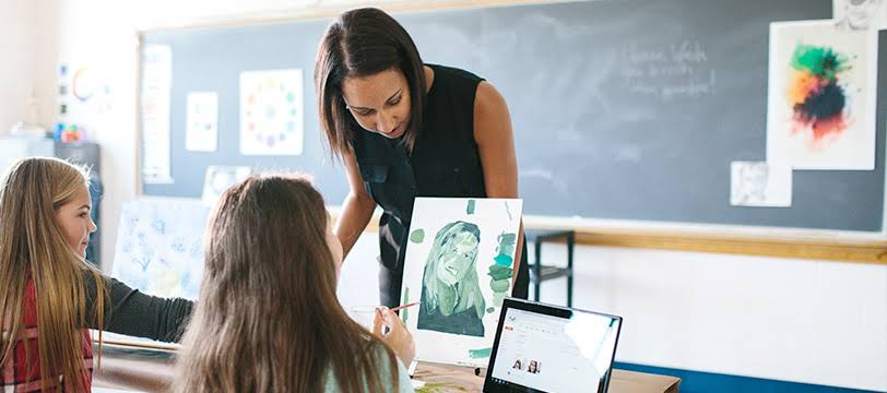 In an arts class, the teacher looks at the artistic work of one of her students.