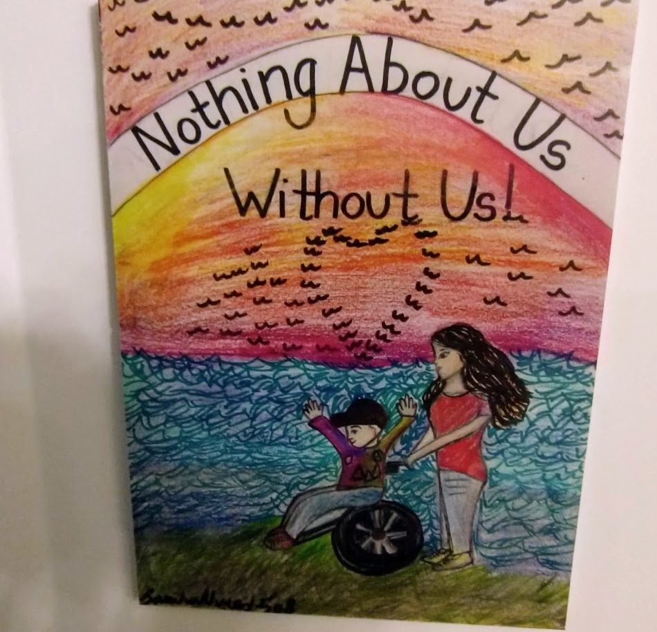 Student art at the ocean with a girl standing with her hands on the wheelchair with a boy sitting in it. There are birds and a rainbow in the sky. In the rainbow these words are written: Nothing about us without us.